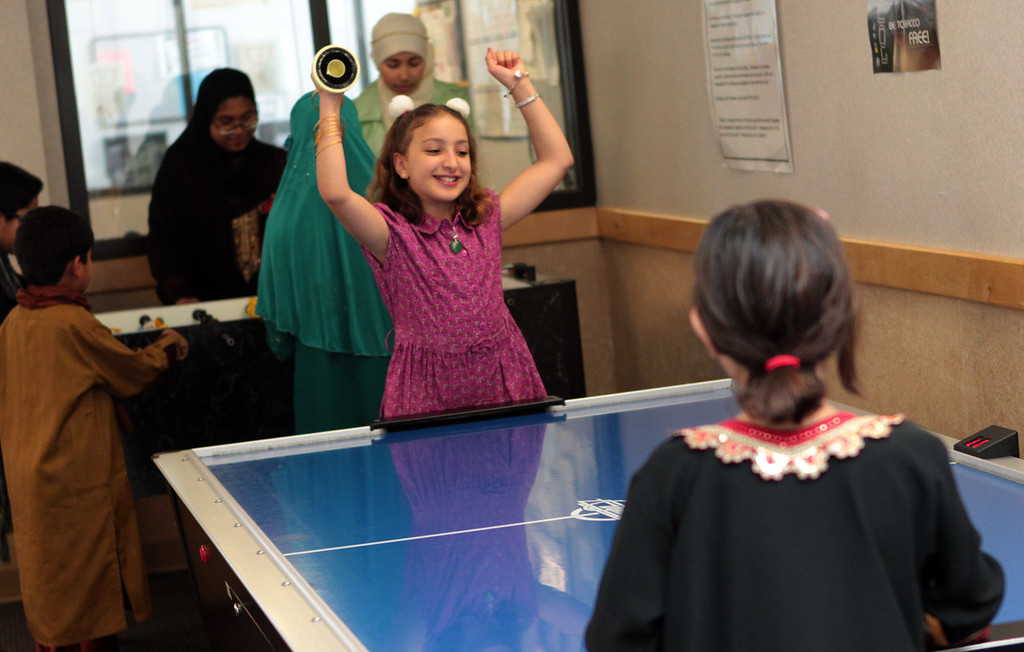 . Riham Ezzerouali, 9, celebrates a point while playing a game of air hockey with Fatima Khawaja , 6, both of Union City during an Eid al-Fitr event at the Silliman Center in Newark, Calif., on Thursday, Aug. 8, 2013. (Anda Chu/Bay Area News Group)