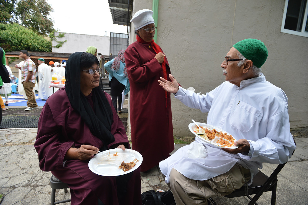 . Arifa Abdullah, standing, visits with Noorie Gulamhussein, left, and Mansurali Nurmuhammad as they enjoy a meal during an Eid al-Fitr celebration at the Naqshbandi Sufi Order Masjid Al Iman mosque in Oakland, Calif. on Thursday, Aug. 8, 2013. (Kristopher Skinner/Bay Area News Group)