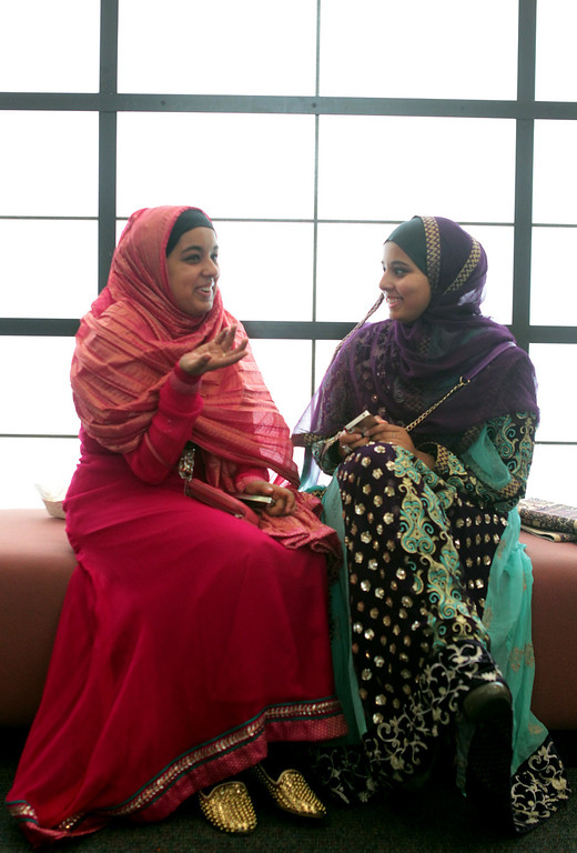 . Sisters, from left, Inaya Ali and Falisha Ali, of Newark, chat during an Eid al-Fitr celebration at the Silliman Center in Newark, Calif., on Thursday, Aug. 8, 2013. (Anda Chu/Bay Area News Group)
