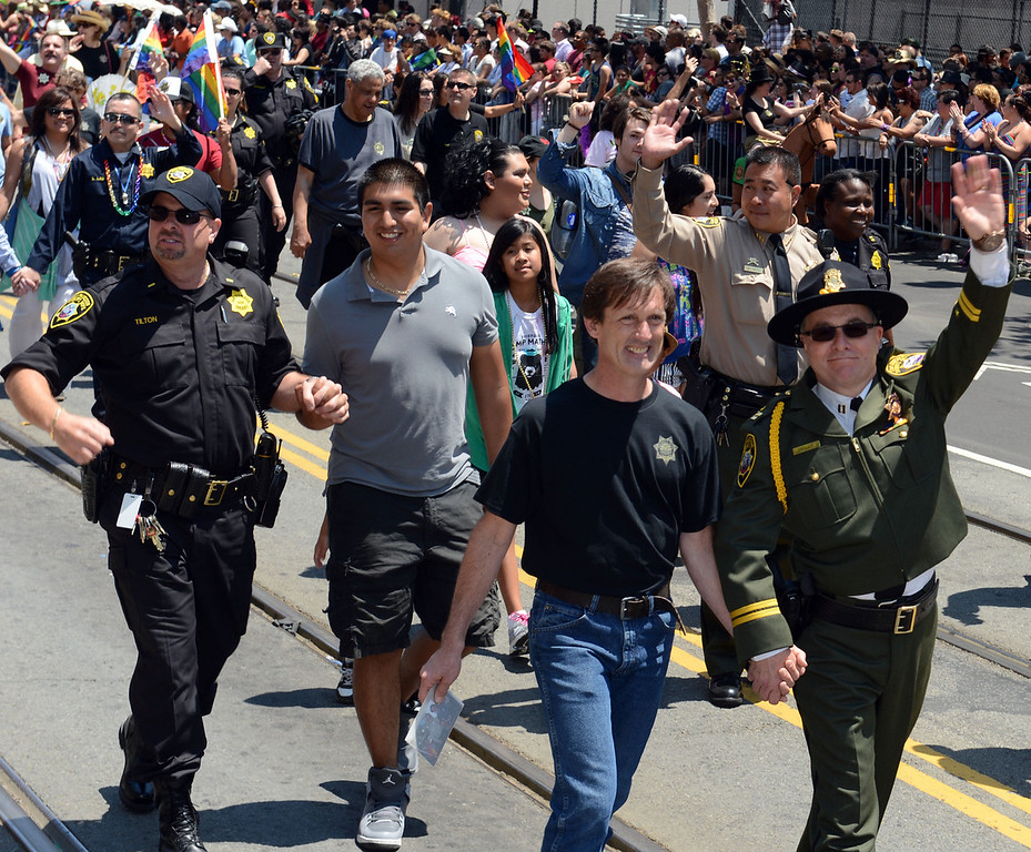 . Members of  law enforcement walk hand-in-hand to the cheers of the crowd during the 42nd San Francisco Pride Celebration and Parade on Market Street in San Francisco, Calif., on Sunday, June 30, 2013. (Susan Tripp Pollard/Bay Area News Group)