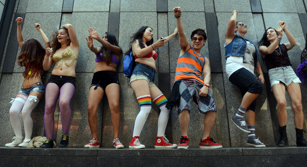. An elevated ledge on a Larkin Street building provides a fine dance floor for these spectators during the 42nd San Francisco Pride Celebration and Parade in San Francisco, Calif., on Sunday, June 30, 2013. Market Street was packed.  (Susan Tripp Pollard/Bay Area News Group)