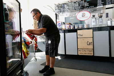 David Lindsay restocks potato chips at his coffee cart at San Jose City Hall in San Jose, Calif., on Wednesday, April 6, 2016. Lindsay has owned the popular coffee cart for almost a decade, but contract disputes with the city has pushed him to close the business. (Gary Reyes/Bay Area News Group)