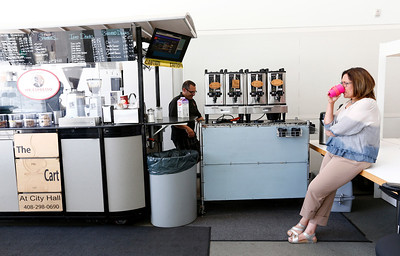 David Lindsay operates his coffee cart as longtime customer, Nandita Modak, finishes her Americano coffee at San Jose City Hall in San Jose, Calif., on Wednesday, April 6, 2016. Lindsay has owned the popular coffee cart for almost a decade, but contract disputes with the city has pushed him to close the business. (Gary Reyes/Bay Area News Group)