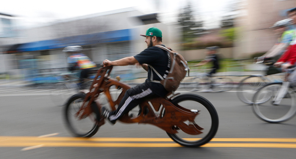 """. Mauro Hernandez, of San Jose, rides the wood-framed  \""""Interceptor\"""" he built at Masterworks during a bike ride in San Jose, Calif., on Sunday, March 9, 2014. Dublin Lord Mayor Oisín Quinn joined cyclists on a seven-mile bicycle ride through the city as part of San Jose-Dublin Sister City Program festivities. Quinn is known for having championed the effort to create a bike sharing service in Dublin much akin to the similar service that\'s sprang up in San Jose and other Bay area cities. (Jim Gensheimer/Bay Area News Group)"""