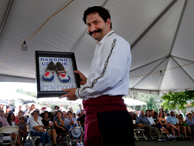 George Panayotopoulos receives an award upon his retirement, recognizing his long years of teaching Greek dance, presented by his sister, Tina Panayotopoulos, before their dance group, the Polemistes, perform at the San Jose Greek Festival Sunday afternoon, June 5, 2016, at Saint Nicholas Greek Orthodox Church, in San Jose, Calif. (Karl Mondon/Bay Area News Group)