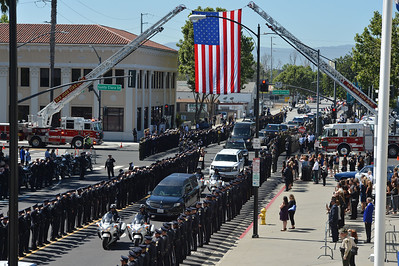 The funeral procession passes under the American flag on the way to a memorial for fallen San Jose police officer Michael Katherman at the SAP Center in San Jose, Calif., on Tuesday, June 21, 2016. Katherman died June 14 when his police motorcycle collided with a minivan at North 10th and Horning streets. He was the city's 13th police officer killed in the line of duty and the second motorcycle officer. (Dan Honda/Bay Area News Group)