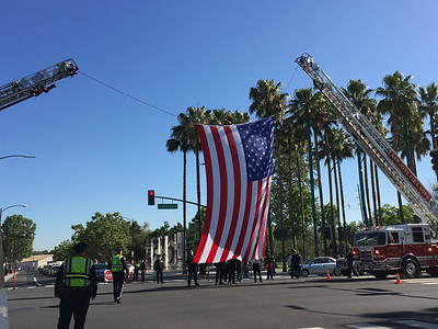 A large American flag is raised between two San Jose Fire Department ladder trucks in the intersection of Santa Clara and Autumn streets in San Jose, Calif., on Tuesday, June 21, 2016, in preparation for the memorial service for fallen San Jose police officer Michael Katherman. (Dan Honda/Bay Area News Group)