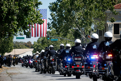 Motorcycle police officers from throughout the state accompany their fallen colleague, San Jose police officer Michael Katherman, in a procession to his memorial service at SAP Center, Tuesday morning, June 21, 2016, in San Jose, Calif. (Karl Mondon/Bay Area News Group)