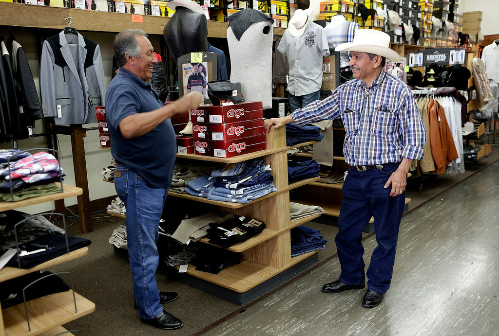 . Jose Mendoza, 76, owner of San Jose Men\'s Wear, right,  chats with longtime customer, Abraham Granados, during the final days before he closes the store for good in San Jose, Calif. on Monday, July 29, 2013.  (Gary Reyes/Bay Area News Group)