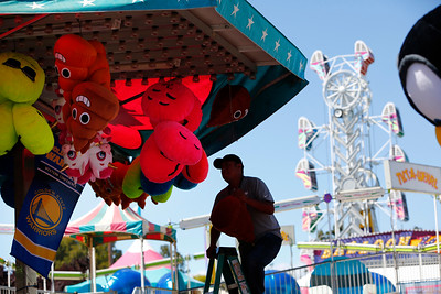 Hector Lovera hangs prizes for the mini-basketball game during final preparations for the opening of the San Mateo County Fair in San Mateo, Calif., on Friday, June 10, 2016.  The fair opens Saturday and runs through Sunday, June 19, 2016. (Gary Reyes/Bay Area News Group)
