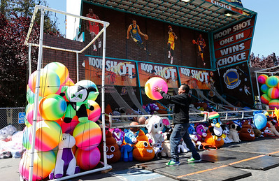 Jose Martinez fills a container with balls at the Hoop Shot game during final preparations for the opening of the San Mateo County Fair in San Mateo, Calif., on Friday, June 10, 2016. The fair opens Saturday and runs through Sunday, June 19, 2016. (Gary Reyes/Bay Area News Group)