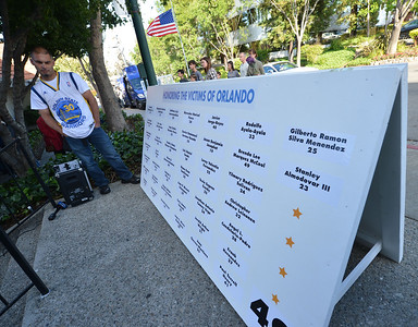 Pete Fonseca, of Walnut Creek, looks at the names of those killed in Orlando during a vigil at the 1220 Club in Walnut Creek, Calif., on Monday, June 13, 2016. The vigil, put on by the 1220 Club, Rainbow Community Center and other LGBT and religious organizations, was in support and to remember those who died in the Orlando shooting. (Dan Honda/Bay Area News Group)