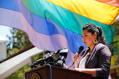 Maribel Martinez reads off the names of the 49 victims who were shot dead in Orlando, Fla., yesterday as the LGBT flag is raised half-mast  behind her at the County Government Center in San Jose, Calif., on Monday, June 13, 2016. A memorial was held to honor the victims of the mass shooting at an Orlando nightclub that occurred early yesterday morning. (Gary Reyes/Bay Area News Group)