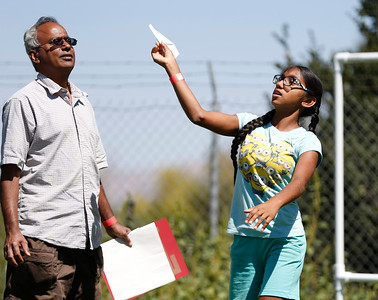 Gan Kumar, watches his daughter Meena Kumar, 11, throw a paper plane at the second annual San Jose Mini Maker Faire at History San Jose Park in San Jose, Calif., on Sunday, September 4, 2016. (Josie Lepe/Bay Area News Group)
