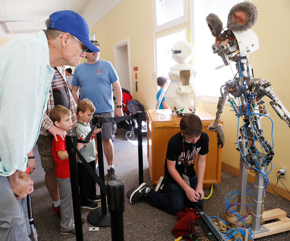 . Mike Mason, left, of Stockton, twins Sam Clayton, 5, center, and Bram Clayton, 5, of San Jose, watch Jack Turner, 13, work on his animatronic robot mouse at the second annual San Jose Mini Maker Faire at History San Jose Park in San Jose, Calif., on Sunday, September 4, 2016. (Josie Lepe/Bay Area News Group)
