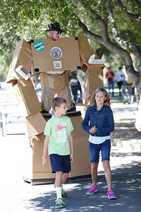 Joshua Bootz, 9, left, and Holly Bootz, 10, of San Jose walk in front of the Jason Lentz, who is wearing giant cardboard robot at the second annual San Jose Mini Maker Faire at History San Jose Park in San Jose, Calif., on Sunday, September 4, 2016. (Josie Lepe/Bay Area News Group)