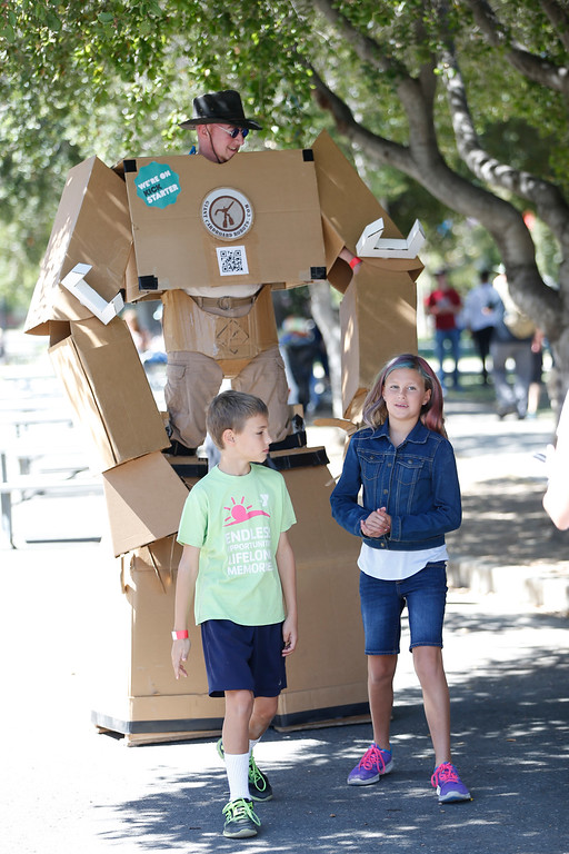 . Joshua Bootz, 9, left, and Holly Bootz, 10, of San Jose walk in front of the Jason Lentz, who is wearing giant cardboard robot at the second annual San Jose Mini Maker Faire at History San Jose Park in San Jose, Calif., on Sunday, September 4, 2016. (Josie Lepe/Bay Area News Group)
