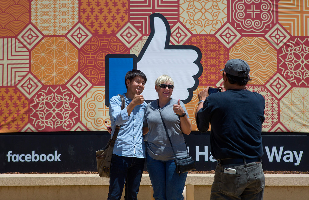 . Ray Santiago, of San Francisco, takes a photo of his friends, Eiji Matsumoto, of Japan, and Tania Houchin, of Sacramento, in front of the sign outside Facebook headquarters at 1 Hacker Way, in Menlo Park, Calif., Friday, May 27, 2016. Tech tourism has become prevalent in the past few years at Silicon Valley icons.  (Patrick Tehan/Bay Area News Group)