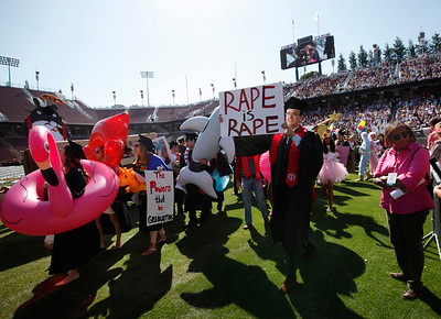 "Paul Harrison carries a ""Rape is Rape"" sign into the Stanford University commencement ceremony in Stanford, Calif., Sunday morning, June 12, 2016. Harrison's protest was one of only a few visible signs of the controversy that has rocked the campus since former Stanford swimmer Brock Turner received a six-month sentence for sexual assault. (Karl Mondon/Bay Area News Group)"