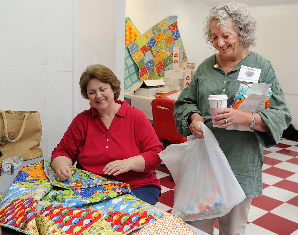""". Quilter Christie Batterman of San Ramon, left,  and organizer of the \""""Doll Day\"""" event  Caroline Archer of Greenbrae share a laugh and a smile when Batterman brings Archer a present of more fabric at The Cotton Patch in Lafayette, Calif., on Tuesday, Sept. 10, 2013. More than 1000 little doll-sized items are being made by sewing and knitting volunteers from Contra Costa County and beyond. The items will be distributed to four Bay Area hospitals (Susan Tripp Pollard/Bay Area News Group)"""