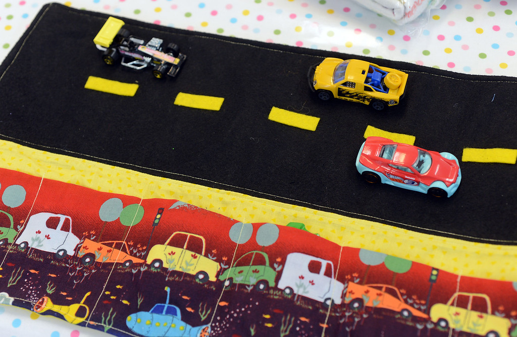 """. A race car track that fits on a hospital tray and provides pockets for storage of hot wheel cars is one of the items made during a \""""Doll Day\"""" event held at The Cotton Patch in Lafayette, Calif., on Tuesday, Sept. 10, 2013. The items will be distributed to boys and girls requiring extended stays in hospitals.  (Susan Tripp Pollard/Bay Area News Group)"""