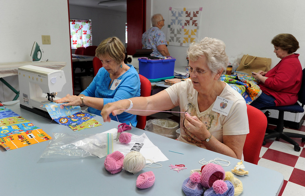 """. Tina de Man of Walnut Creek works on making pom poms for small doll stocking caps, center, while Patti Owen of Martinez, left, Inge Simms of Lafayette, rear center, and Christie Batterman of San Ramon, right, work on children and doll quilts during a \""""Doll Day\"""" event held at The Cotton Patch in Lafayette, Calif., on Tuesday, Sept. 10, 2013. Volunteers meet once a month at the shop to make items for the children requiring long stays at area hospitals. (Susan Tripp Pollard/Bay Area News Group)"""