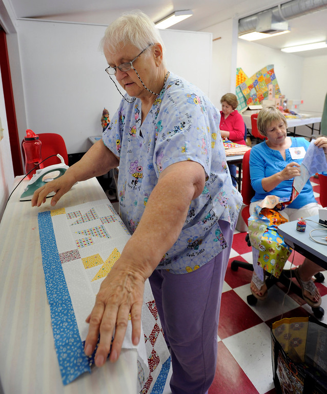 """. Inge Simms of Lafayette smooths out the fabric on a \'Sister\'s Choice\"""" patterned doll quilt before pressing it at a \""""Doll Day\"""" event held at The Cotton Patch in Lafayette, Calif., on Tuesday, Sept. 10, 2013.The items will be distributed along with dolls to young girls requiring extended stays in hospitals.  (Susan Tripp Pollard/Bay Area News Group)"""
