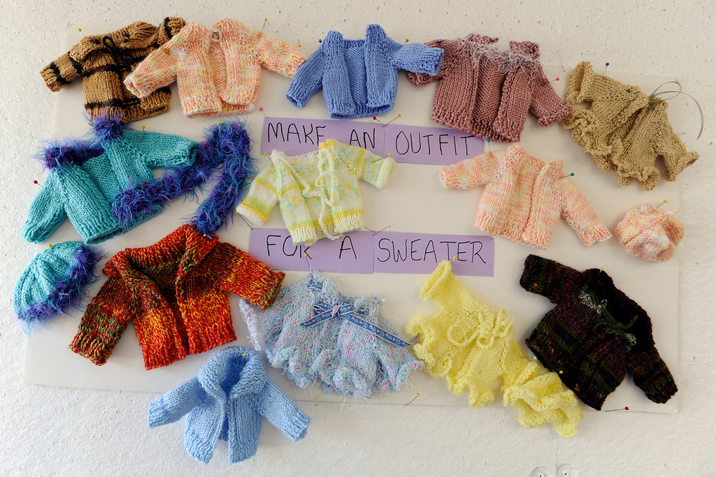 """. Finished hand knitted doll sweaters on display serve as inspiration to volunteers sewing and knitting during a \""""Doll Day\"""" event held at The Cotton Patch in Lafayette, Calif., on Tuesday, Sept. 10, 2013.  (Susan Tripp Pollard/Bay Area News Group)"""
