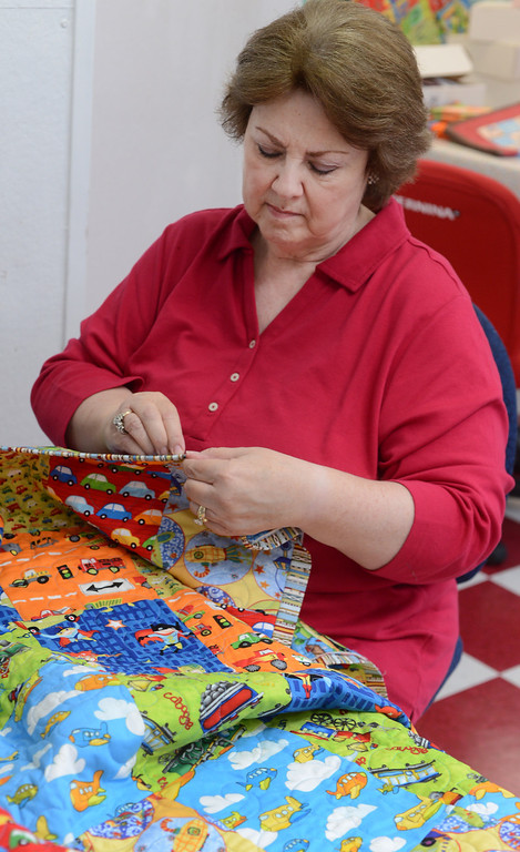 """. Bright bold colors make up a boys quilt to be donated as Christie Batterman of San Ramon hand sews the binding during a \""""Doll Day\"""" event held at The Cotton Patch in Lafayette, Calif., on Tuesday, Sept. 10, 2013. The items will be distributed along with dolls to young girls and boys requiring extended stays in hospitals.  (Susan Tripp Pollard/Bay Area News Group)"""