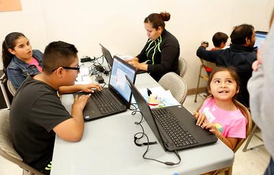 Michael Matadamas, left, mom Annayelle Matadamas, center right,  and Allison Matadamas, 5, right, work on their computer skills during Earth Day event at Santee Elementary School in East San Jose, Calif., on Sunday, April 3, 2016. (Josie Lepe/Bay Area News Group)