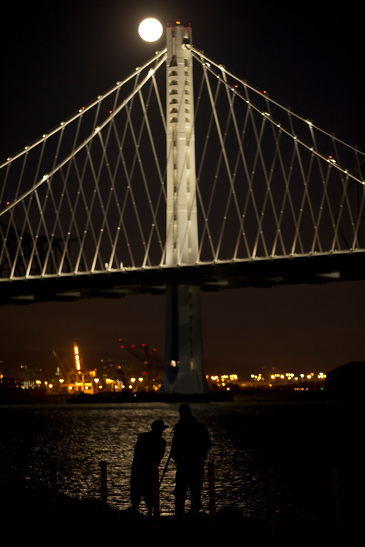 """. A pair of photographers are silhouetted against the waters of the San Francisco Bay as the full moon rises over the Bay Bridge, as seen from Treasure Island in San Francisco, Monday, Sept. 8, 2014. The full moon is the last so-called \""""supermoon\"""" of the summer. (D. Ross Cameron/Bay Area News Group)"""