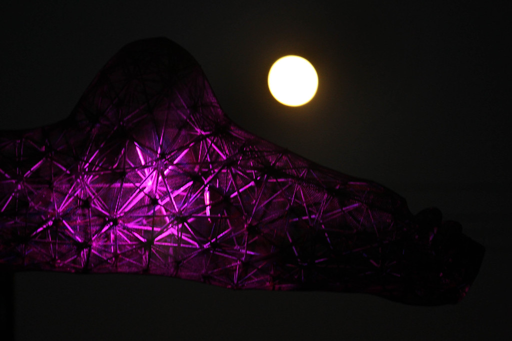 . The foot of the Bliss Dance sculpture by Marco Cochrane is lightened from inside the structure as  the full moon rises on the horizon seen from Treasure Island in San Francisco, Calif., on Monday, Sept. 8, 2014. The harvest moon and the last supermoon of the year was clearly seen in the East Bay.  (Ray Chavez/Bay Area News Group)