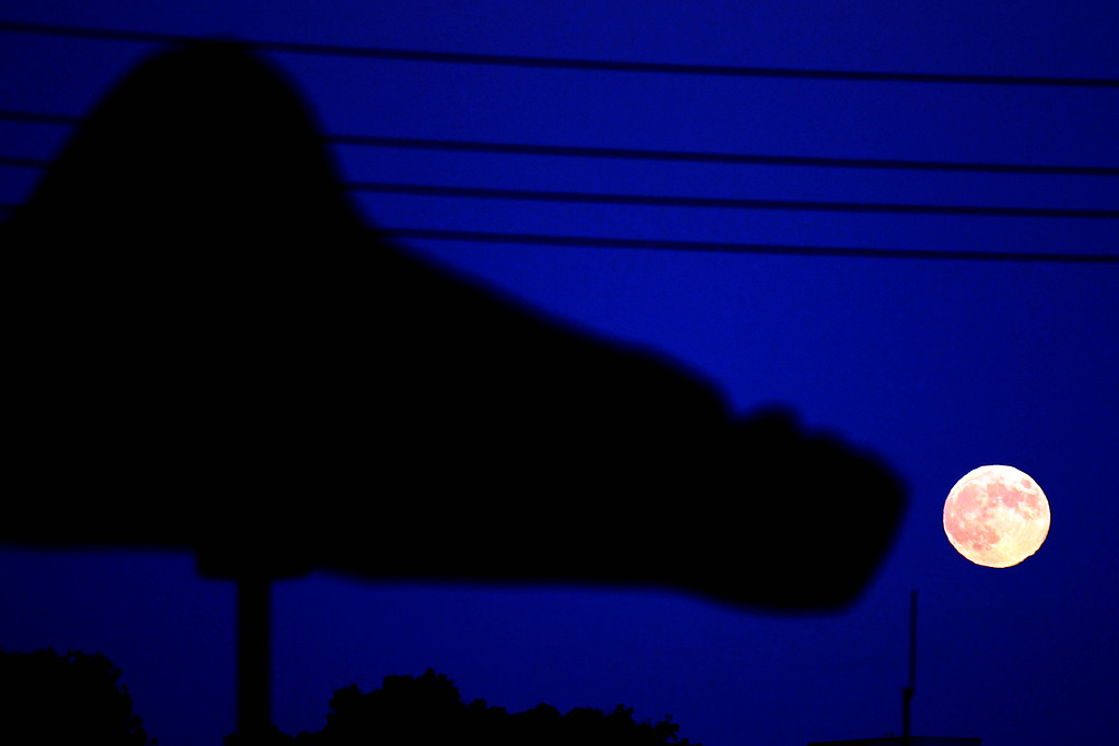 . The foot of the Bliss Dance sculpture by Marco Cochrane is silhouetted by the full moon as it rises on the horizon seen from Treasure Island in San Francisco, Calif., on Monday, Sept. 8, 2014. The harvest moon and the last supermoon of the year was clearly seen in the East Bay.  (Ray Chavez/Bay Area News Group)