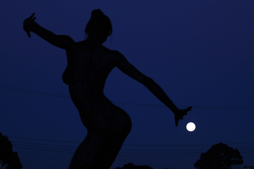 . The Bliss Dance sculpture by Marco Cochrane dances to the full moon as it rises on the horizon  at Treasure Island in San Francisco, Calif., on Monday, Sept. 8, 2014. The harvest moon and the last supermoon of the year was clearly seen in the East Bay.  (Ray Chavez/Bay Area News Group)