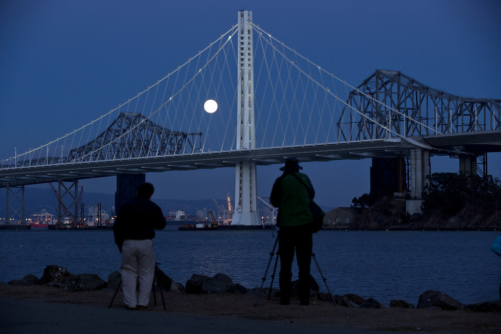 """. Photographers shoot the full moon as it rises over the Bay Bridge, as seen from Treasure Island in San Francisco, Monday, Sept. 8, 2014. The full moon is the last so-called \""""supermoon\"""" of the summer. (D. Ross Cameron/Bay Area News Group)"""