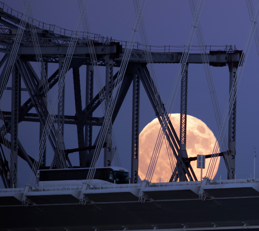 """. A tour bus appears to drive into the full moon as it rises over the Bay Bridge, as seen from Treasure Island in San Francisco, Monday, Sept. 8, 2014. The full moon is the last so-called \""""supermoon\"""" of the summer. (D. Ross Cameron/Bay Area News Group)"""
