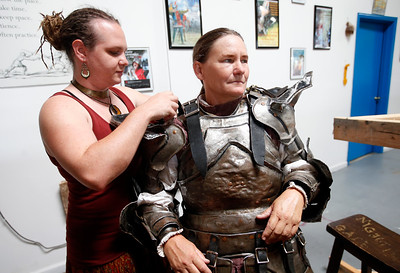 Amy Farrell, right, gets help from her squire, Megan Doyle, getting into her armor for a tournament at the Davenriche European Martial Artes School in Santa Clara, Calif., Sunday, July 31, 2016. (Karl Mondon/Bay Area News Group)