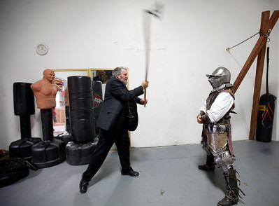 Steaphen Fink uses a 12th-century Danish axe replica to deliver a blow to the helmet of Amy Farrell getting ready to compete at the Davenriche European Martial Artes School tournament in Santa Clara, Calif., Sunday, July 31, 2016. (Karl Mondon/Bay Area News Group)