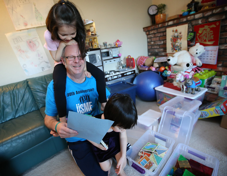 Derrall Garrison, left, plays with his daughters Abby, 6, and Megan, 4, right, in their home on Monday, March, 14, 2016, in Castro Valley, Calif.  Garrison, who is a teacher at R.I. Meyerholz Elementary School in San Jose, is unable to afford housing in the South Bay and commutes daily to work from Castro Valley.  (Aric Crabb/Bay Area News Group)