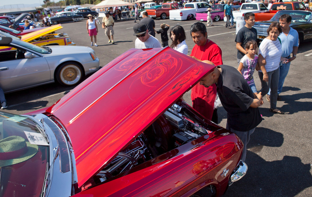 . Visitors check out a 1965 Chevy on display during the Fifth Annual Blvd. Bombs car show and fundraiser in San Jose Saturday, Sept. 14, 2013. The event featured a car show of vintage, classic and custom cars and street rods and lowriders. The benefits go to Second Harvest Food Bank, City Team Ministries and local homeless advocacy organizations. There were also numerous bands playing and vendors selling food of all kinds. (Patrick Tehan/Bay Area News Group)