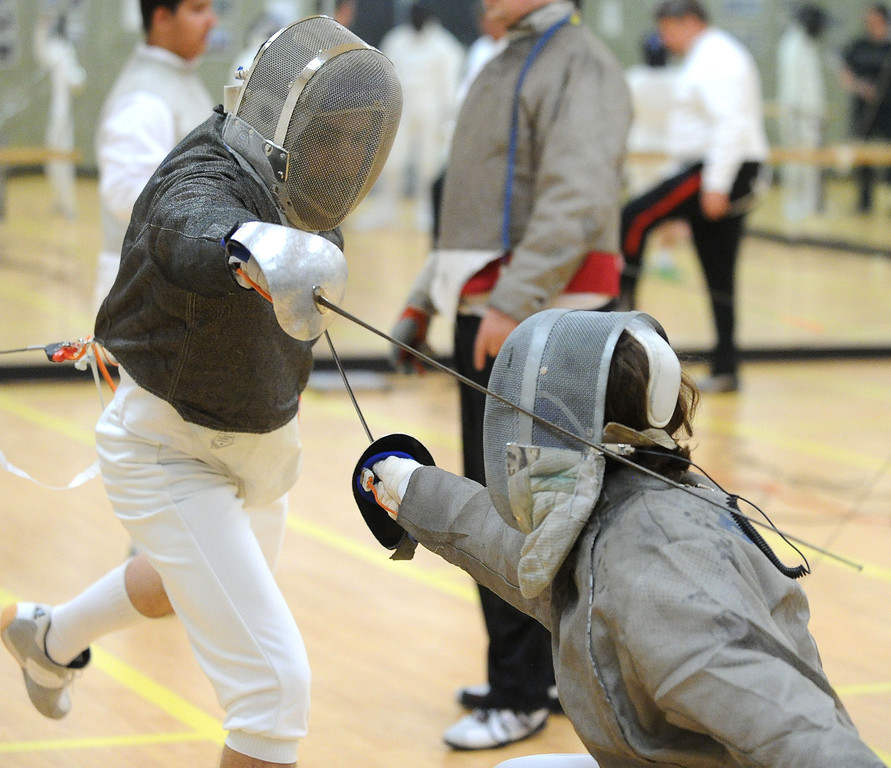 . Darian Drake, of Dublin, left, and Andy Faubert, of Danville, have a saber match during the Las Positas Fencing Center\'s Level II Saber class for adults held at Las Positas College in Livermore, Calif., on Tuesday, July 9, 2013. The fencing center is operated through the Las Positas College Community Education program and offers instruction in foil, epee and saber. The center offers classes in all levels of fencing for adults and children over the age of 8. (Doug Duran/Bay Area News Group)