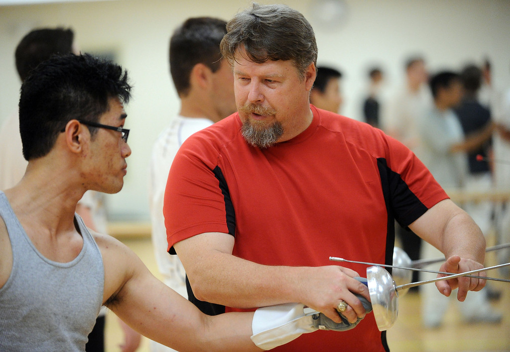. Fencing instructor Jim Ringener, of Hayward, gives some fencing tips during the Las Positas Fencing Center\'s class for adults held at Las Positas College in Livermore, Calif., on Tuesday, July 9, 2013. The fencing center is operated through the Las Positas College Community Education program and offers instruction in foil, epee and saber. The center offers classes in all levels of fencing for adults and children over the age of 8. (Doug Duran/Bay Area News Group)