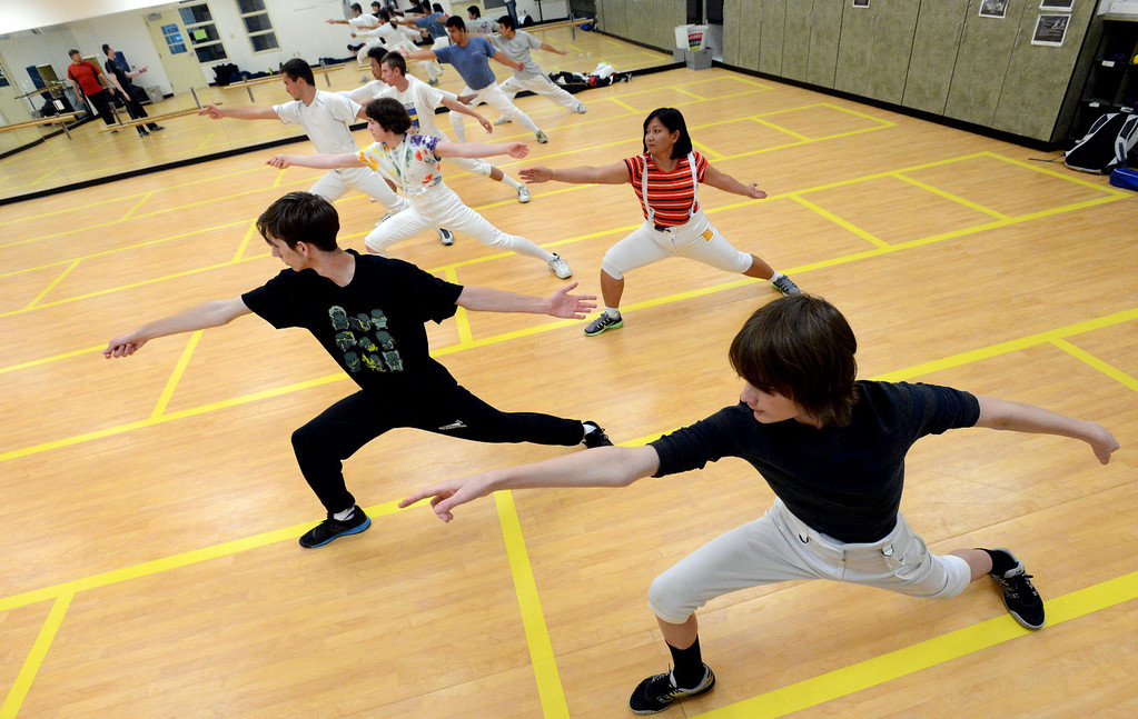 . Members of the Las Positas Fencing Center\'s adult class  practice fencing moves during the beginning of the class held at Las Positas College in Livermore, Calif., on Tuesday, July 9, 2013. The fencing center is operated through the Las Positas College Community Education program and offers instruction in foil, epee and saber. The center offers classes in all levels of fencing for adults and children over the age of 8. (Doug Duran/Bay Area News Group)