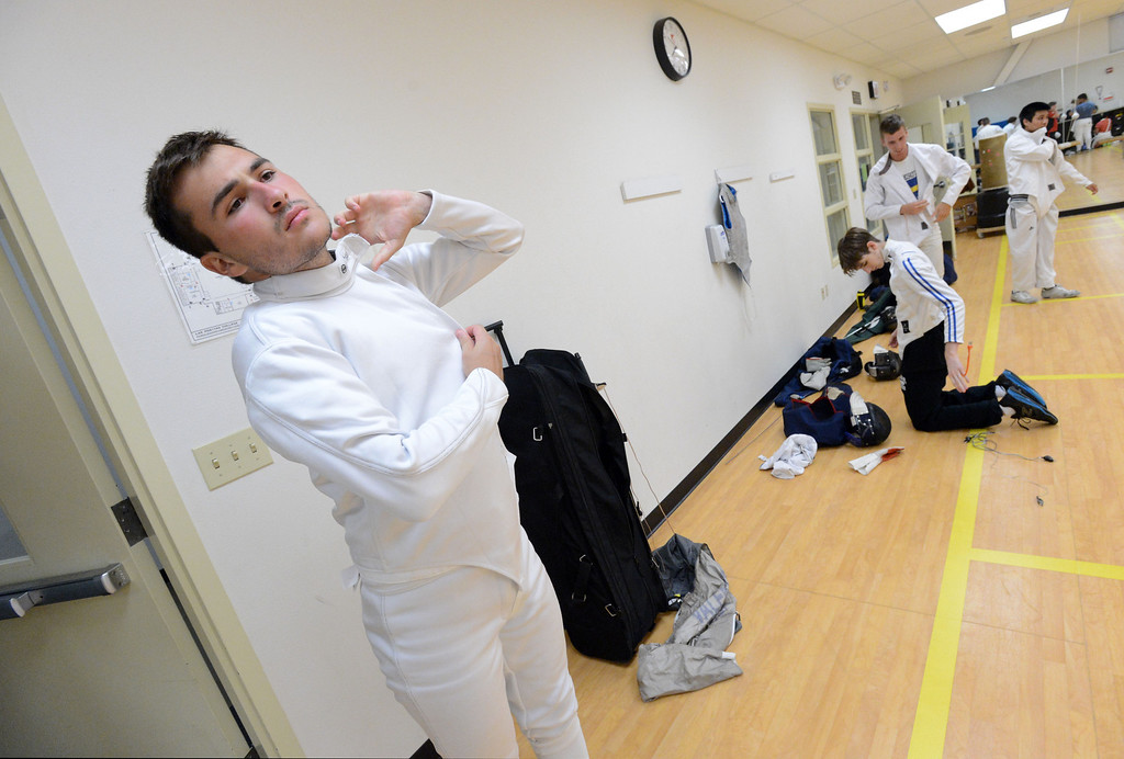 . Michael Valente, of Danville, puts on his fencing safety equipment before a saber match during the Las Positas Fencing Center\'s adult class held at Las Positas College in Livermore, Calif., on Tuesday, July 9, 2013. The fencing center is operated through the Las Positas College Community Education program and offers instruction in foil, epee and saber. The center offers classes in all levels of fencing for adults and children over the age of 8. (Doug Duran/Bay Area News Group)