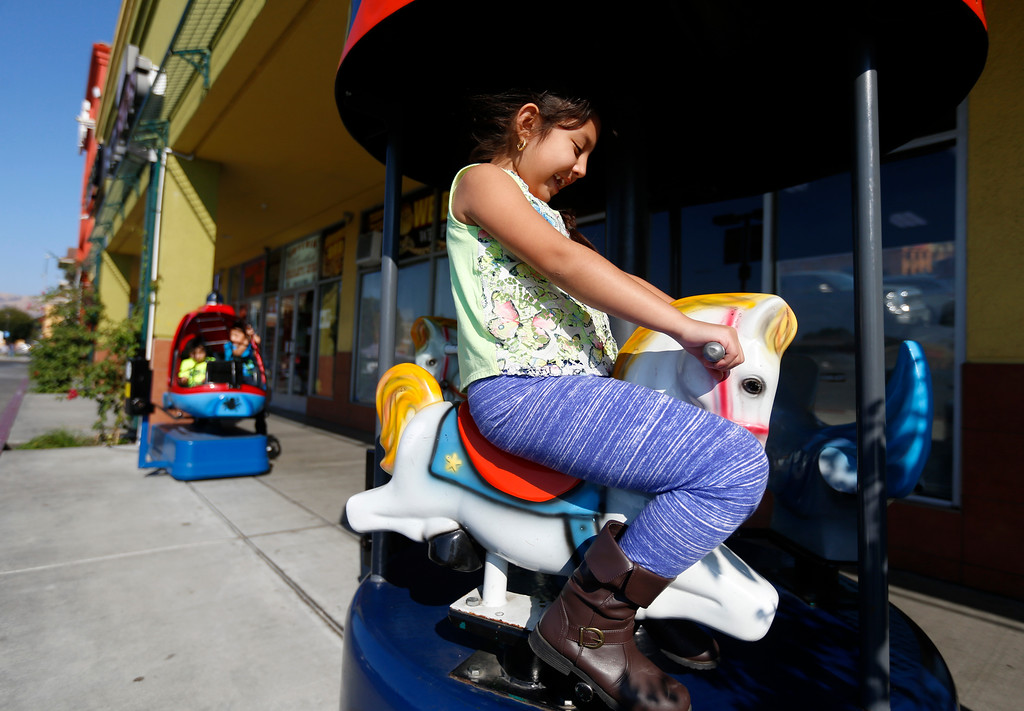 . Renee Navarrete, 6, from San Jose, rides a carousel outside of La Placita Tropicana Shopping Center in San Jose, Calif., on Thursday, August 25, 2016. Her brothers, left, Ronny, 2, and Reily, 5, ride the helicopter. (Nhat V. Meyer/Bay Area News Group)