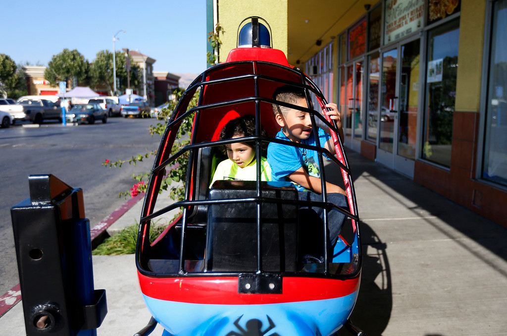 . Ronny Navarrete, 2, left, and his brother Reily Navarrete, 5, from San Jose, ride a helicopter outside of La Placita Tropicana Shopping Center in San Jose, Calif., on Thursday, August 25, 2016. (Nhat V. Meyer/Bay Area News Group)
