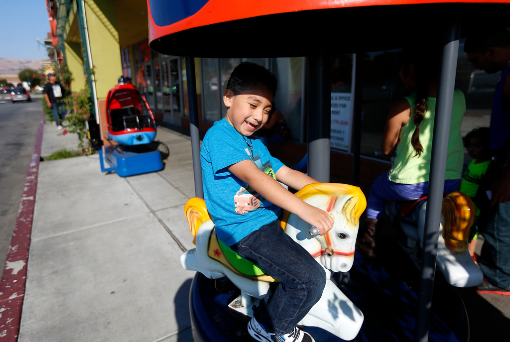 . Reily Navarrete, 5, center, and his sister Renee Navarrete, 6, from San Jose, ride a carousel outside of La Placita Tropicana Shopping Center in San Jose, Calif., on Thursday, August 25, 2016. (Nhat V. Meyer/Bay Area News Group)