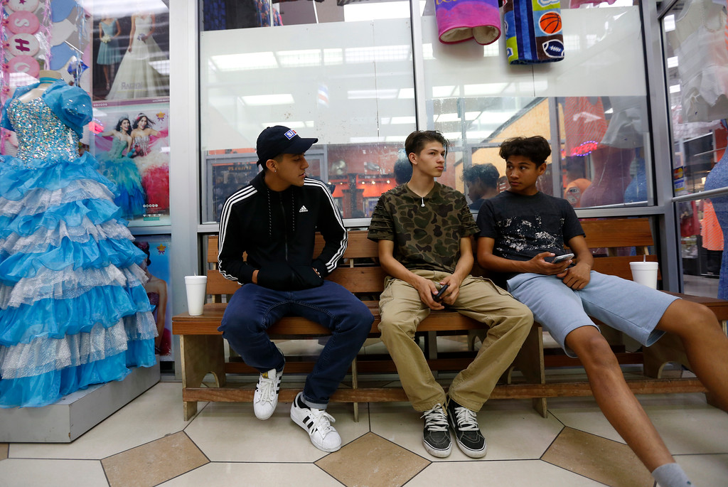 . From left to right, Alex Guevara, Luis Langarica and Alexis Pineda, each 17 years-old from San Jose, wait to get their hair cut inside of La Placita Tropicana Shopping Center in San Jose, Calif., on Thursday, August 25, 2016. (Nhat V. Meyer/Bay Area News Group)