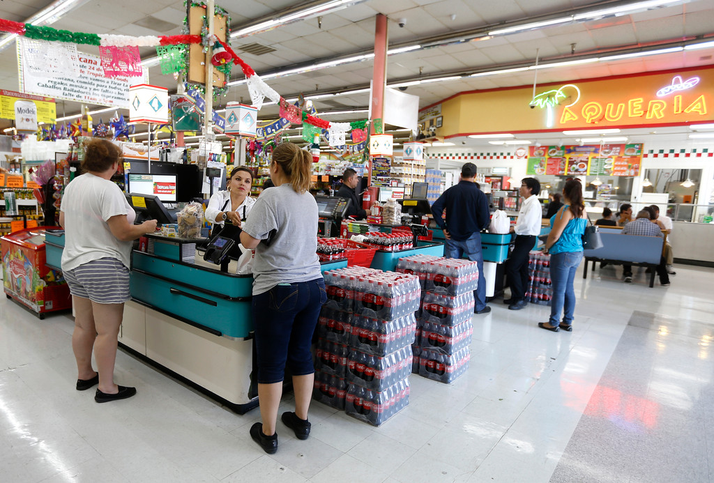 . Cashier Susan Lopez, left, helps customers at Tropicana Foods in San Jose, Calif., on Thursday, August 25, 2016. (Nhat V. Meyer/Bay Area News Group)