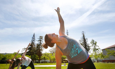 Taryn Mason, right, enjoys yoga in the sunshine during a group class in the quad at San Jose State University, in San Jose, Calif., on Wednesday, April 6, 2016. Be the Change Yoga holds a free class on campus once month for students and the public. (Gary Reyes/Bay Area News Group)